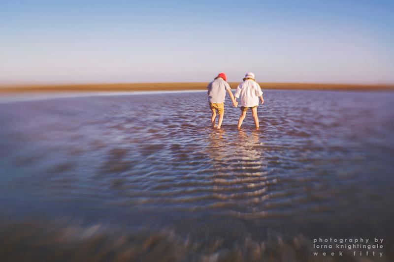 twin-boys-holding-hands-on-a-beach